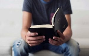 man in jeans reading bible
